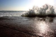 Waves crashing onto a side road