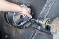Operator measuring drilled parts