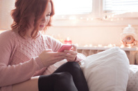 Redhead woman laughing and texting  in bed