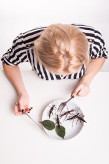 Woman eating insects with a fork in a restaurant