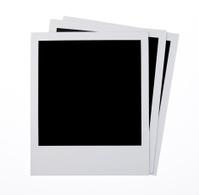 Three blank instant camera photo prints