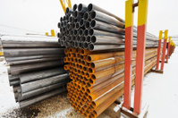 pile of construction pipes in outdoor warehouse