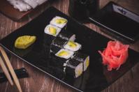 vegetarian avocado sushi roll on black plate