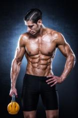 Muscular man holding yellow kettlebell