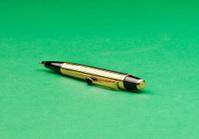 Golden pen lying on green background