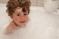 Small boy enjoying a bath of bubbles.
