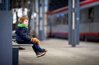 Cute boy, sitting on a bench with teddy bear