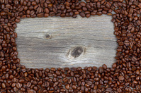 Border of freshly roasted coffee beans on aged wood