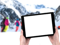 tablet in hands and people skiing in the background