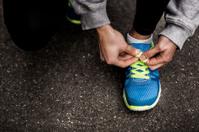Runner Tying Shoelaces In The Road