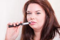 Woman smoking e-cigarette on a white background