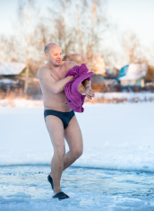 man wipes a towel after swimming in  water at frosty