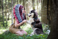 Indian girl in war bonnet playing with husky dog