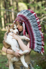 Indian girl in war bonnet playing with husky dog in forest