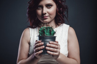 Young woman holding a cactus
