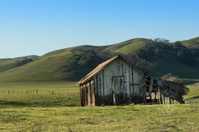 Abandoned Farm Building With Hills in Background