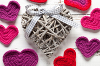 Crochet and wicker hearts on white table