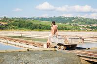 man working in salt flats near portoroz, slovenia