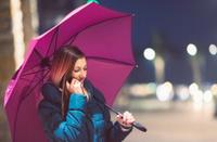 Teenager on the phone on a rainy night