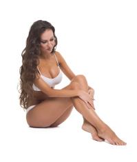 Pretty woman runs hand over smooth skin of feet