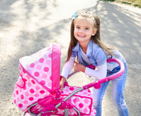 Cute smiling little girl playing with her toy carriage