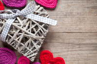 Crochet and wicker hearts on wooden table