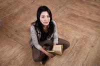 Asian girl reading on floor