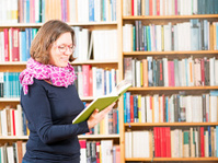 Woman reading in front of bookshelves