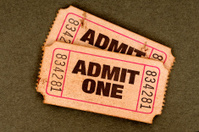 Pair of old torn admit one movie tickets.