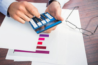 Close up of finger using calculator at desk