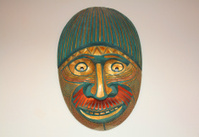 Tribal mask hung in white wall