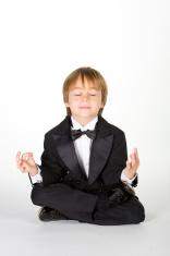 Little boy wearing a tuxedo in meditation