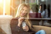 female drink coffee under sunlight