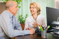 Elderly doctor talking with elderly male patient