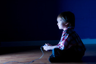 Little boy plays video game in the dark