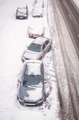 Snow-covered cars on the roadside