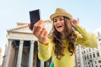 Happy young woman making selfie near pantheon in rome, italy