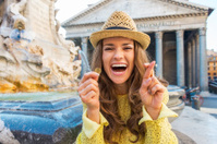 Woman with crossed fingers and coin near fountain in rome