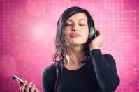 Happy calm girl enjoying listening to music with earphones.
