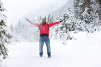 Happy young man with snow glasses throws up snow