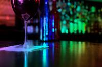 Wine glass on bar in night club.  Colorful lighting.