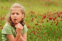 Girl enjoying red lollipop in crimson clover field