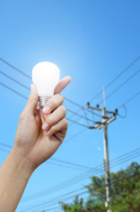 hand with light bulb, electricity pole background