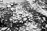 Frozen riverbed with snowy rocks in winter