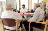 elderly couple sitting in doctors room