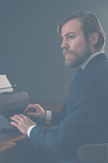 Retro businessman sitting at a typewriter