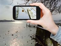 tourist taking photo of Lake Geneva in winter