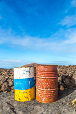 old rusty colorful barrels in volcanic landscape in Timanfaya