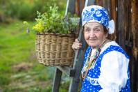 Slavic happy elderly woman in ethnic clothes outdoor