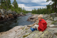 Boy sitting close to a river in wilderness